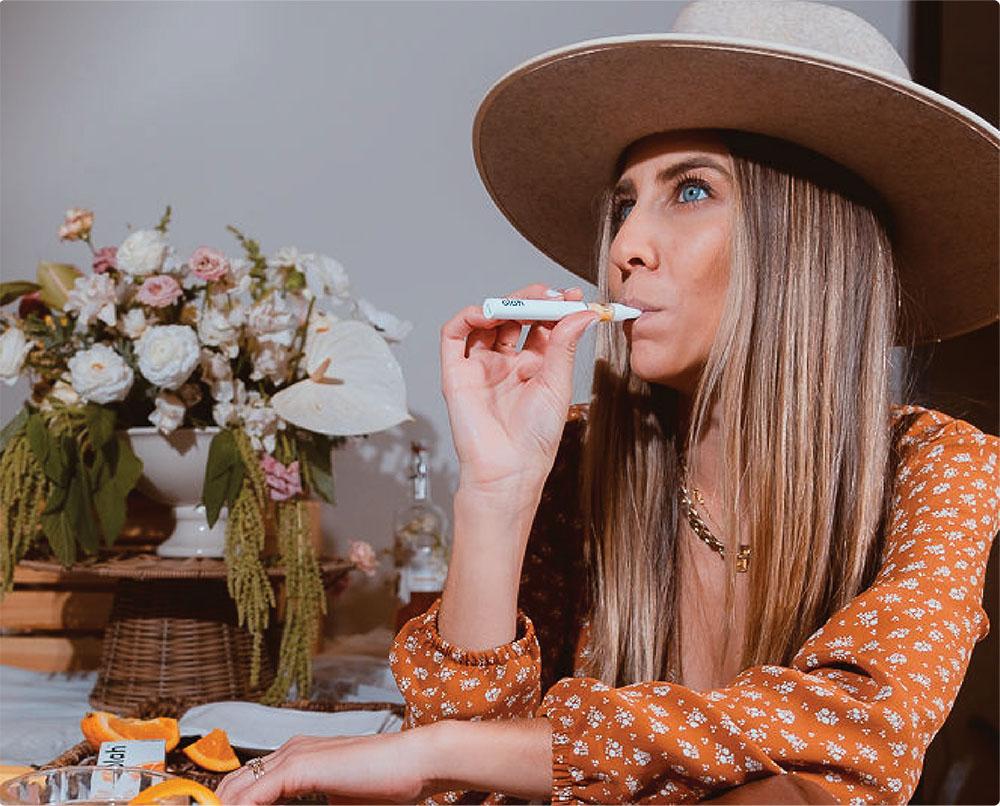 Woman using tangerine vape flavor